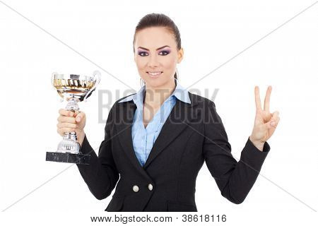 Happy young business woman holding a trophy and making a victory gesture, over white background