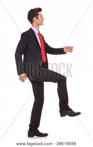 side view of a business man stepping up and moving forward against a white background