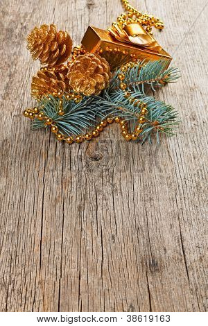 Christmas golden decorations on pine branch on wooden background