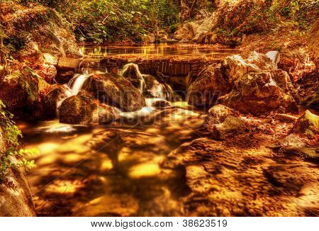 Beautiful waterfall in forest, wonderful view of cascade river, peaceful jungle mountains, wild nature landscape, dry autumn trees, water stream in rainforest with yellow old falling leaves