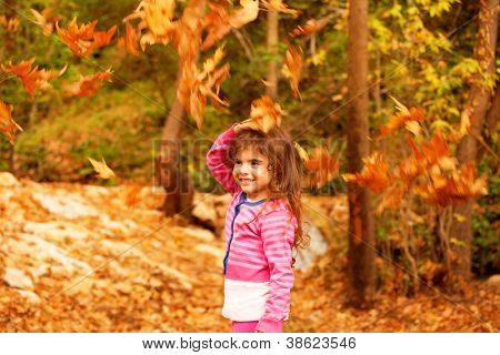Photo of sweet little girl in autumn forest, adorable child playing game in fall park, pretty kid enjoying autumnal nature, beautiful golden trees foliage, nice warm sunny day