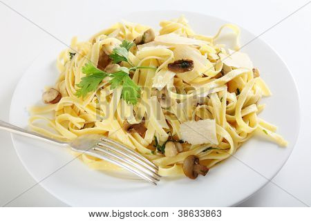 Ribbon pasta with mushrooms and italian parsley, fettuccine ai funghi, topped with curls of parmesan reggiano and with a fork