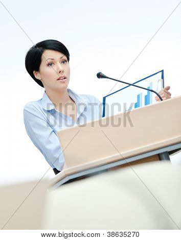 Female executive at the podium handing diagram. Business conference