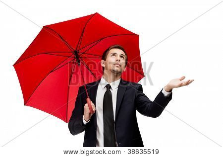 Palming up business man with opened umbrella checks the rain, isolated on white