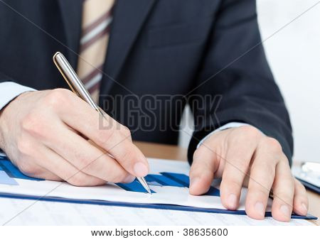 Executive working with diagrams. Close up of hands and documents