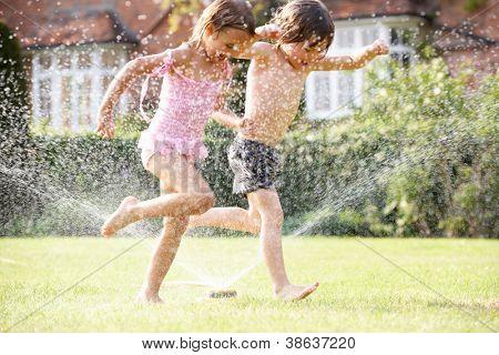 Two Children Running Through Garden Sprinkler