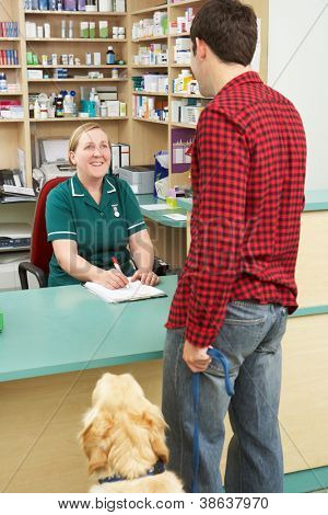 Man Making Appointment At Reception Of Veterinary Surgery
