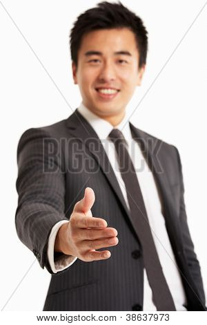 Studio Portrait Of Chinese Businessman Reaching Out To Shake Hands
