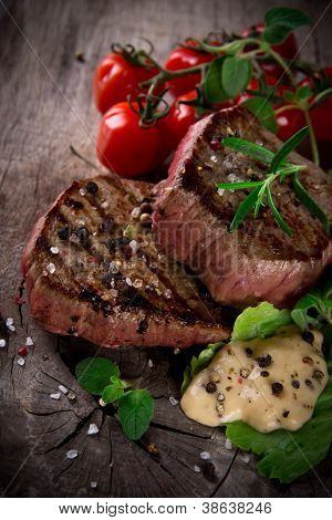 Grilled bbq steaks with fresh herbs and tomatoes