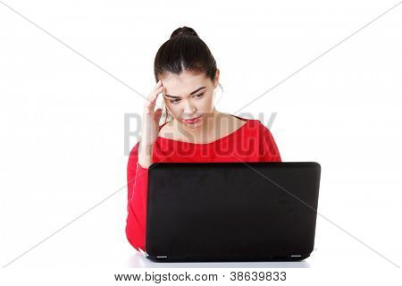 Sad woman looking on laptop screen. Isolated on white.