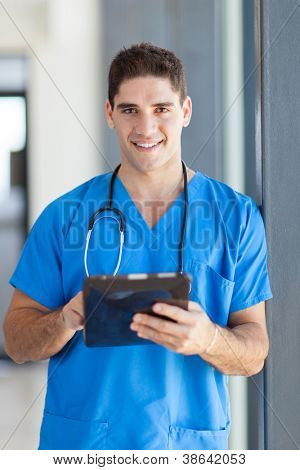 male medical doctor using tablet computer in hospital