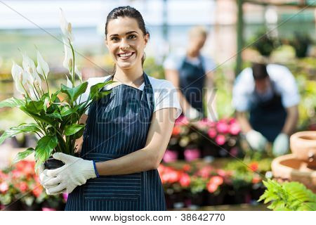 happy female nursery owner with pot of flowers inside greenhouse