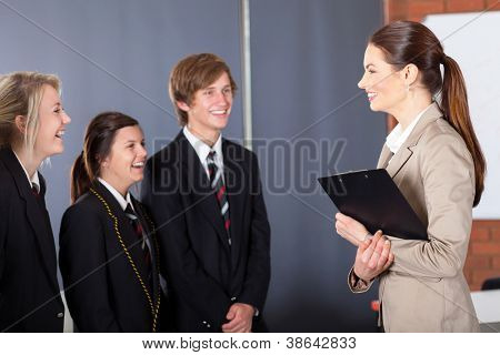happy high school teacher talking to students in classroom