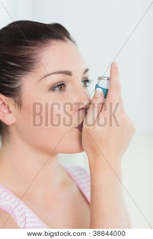 Woman with asthma using an asthma inhaler for preventing attacks