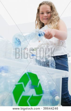 Little girl throwing bottles into recycling box