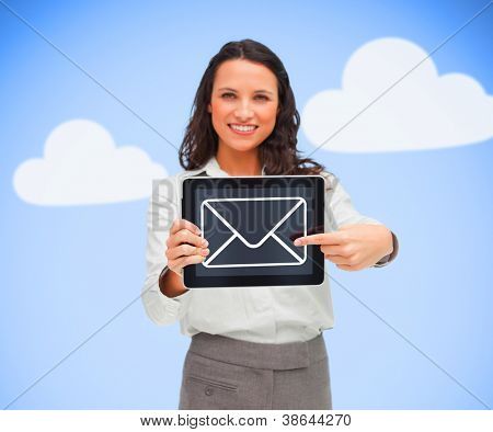 Businesswoman standing holding a tablet computer showing mail symbol while smiling on blue cloud background