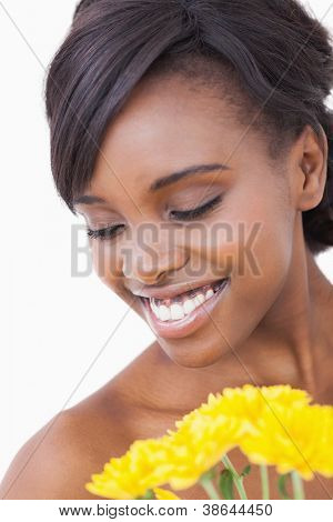Woman is smiling while holding yellow flowers on white background