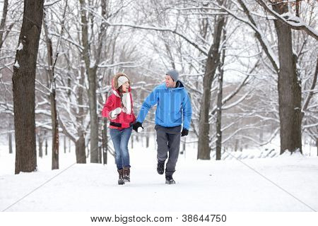 Couple walking and running in winter forest happy and joyful holding hands on romantic date in winter snow forest landscape. Cheerful interracial young couple, Asian woman, Caucasian man.