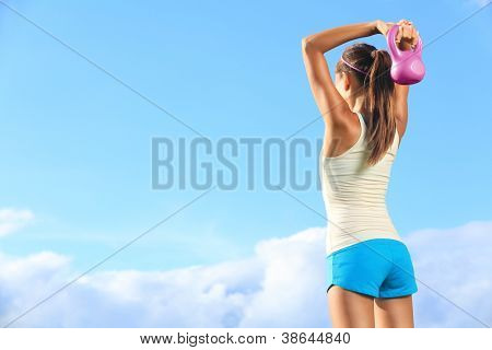 Fitness woman using kettlebells outside during strength training against copyspace.