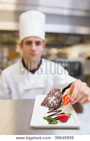 Chef putting a strawberry on dessert plate in the kitchen