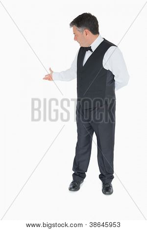 Waiter showing something behing him on white background