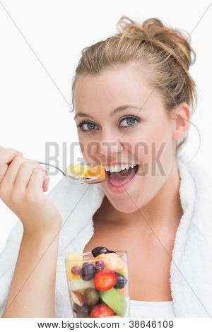 Woman eating fruit salad happily