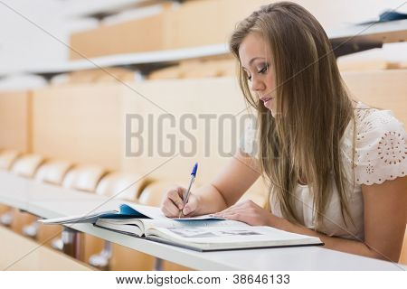 Concentrating woman sitting at the lecture hall while writing out notes