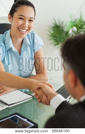 Happy businesswoman shaking man's hand in her office