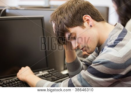 Student sitting sleeping at the computer desk in college
