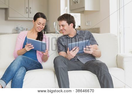 Two people sitting on the couch in the living room while using a tablet computer