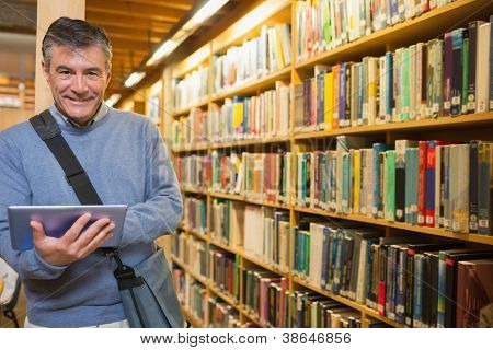 Man smiling while holding tablet pc in the library