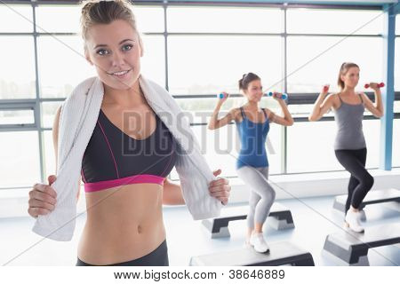 Woman smiling at front of aerobics class in gym