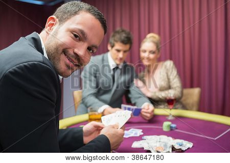 Man smiling and looking up from poker game in casino