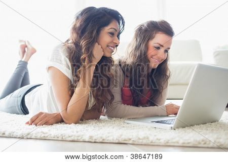 Two women typing on laptop while lying on the floor in a living room