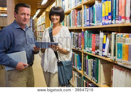Woman and man holding tablet pc standing in library