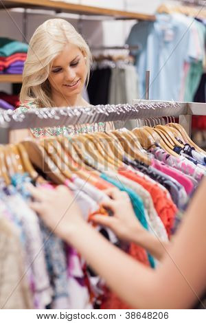 Woman searching at the clothes rack while smiling