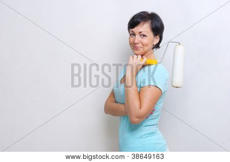 Smiling woman with painting roller