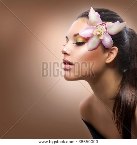 Beauty Portrait. Beautiful Stylish Girl with Orchid Flower. Pastel Colors. Perfect Face Skin