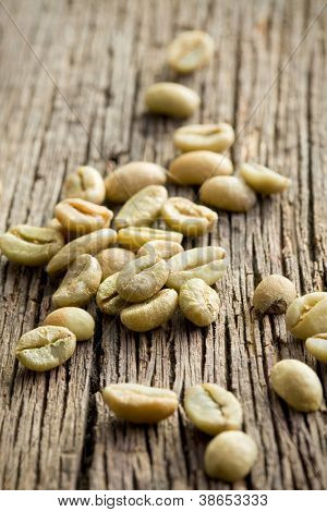 green coffee beans on old wooden table