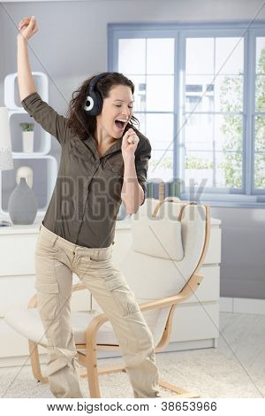 Happy woman singing and dancing with headphones at home, having fun.