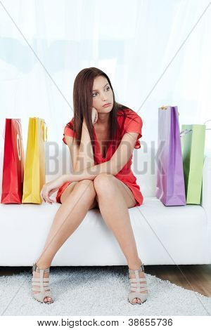 Retrato de shopaholic estressado, sentado no sofá, cercado por paperbags