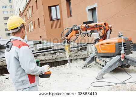 builder worker in safety protective equipment operating construction demolition machine robot
