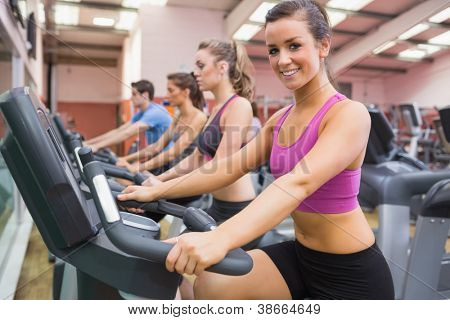 Woman smiling on exercise bicycle in the gym