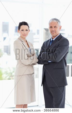 A mature director and his young secretary standing upright in front of the window