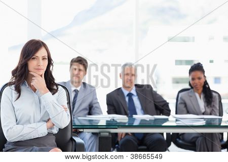Young businesswoman almost smiling with her hand on her chin in a bright meeting room