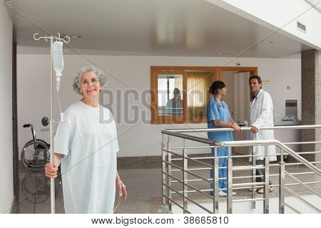 Laughing woman standing in the hallway holding a drip in her hands