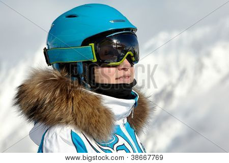 Portrait of young woman in ski suit, helmet and sunglasses, mountains and skilift supports reflected in sunglasses.