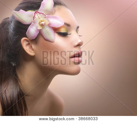 Beautiful Girl with Orchid Flower. Pastel Colors. Perfect Face Skin.Beauty Portrait.