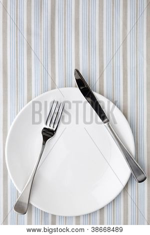 Place setting on striped tablecloth in shades of blue, white and taupe.  Overhead view.