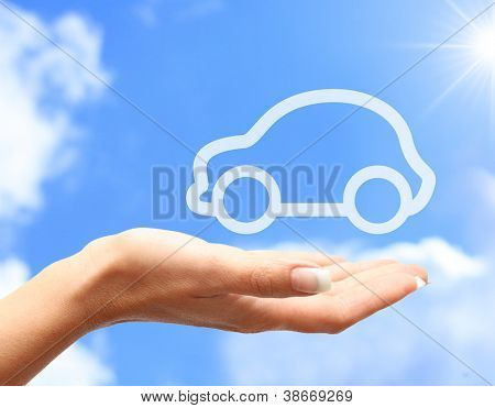 Hand with car against blue sky background